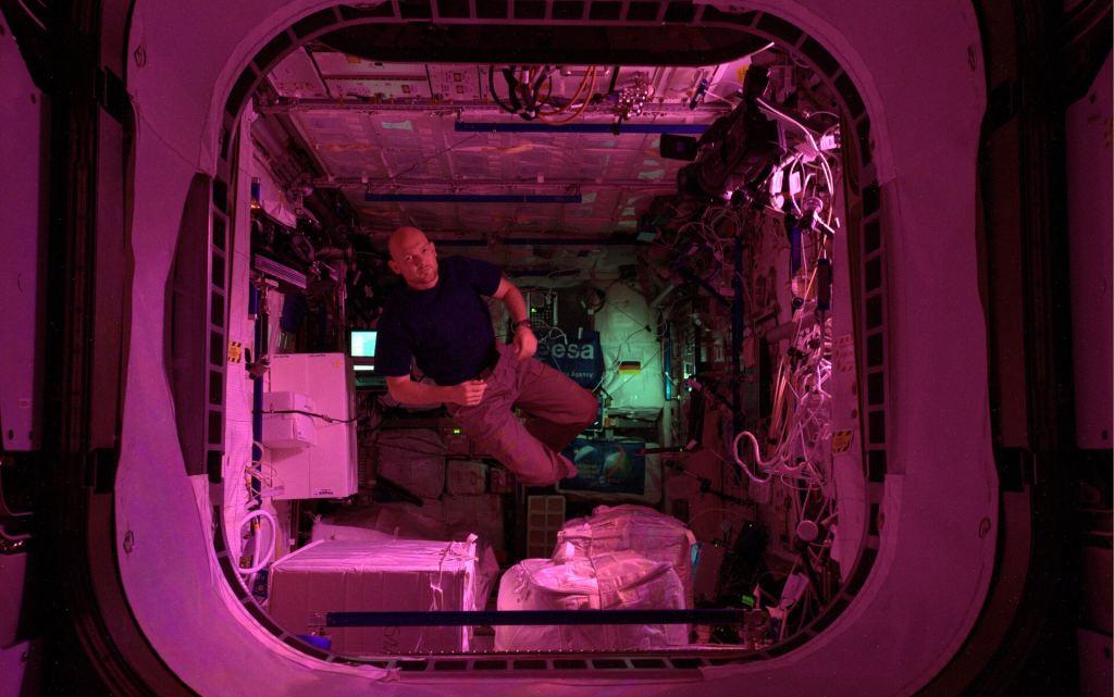 Astronauta che galleggia nel modulo Columbus immerso in una morbida luce rosa.